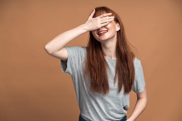 빨간 머리 소녀는 손으로 눈을 감았다. 갈색 바탕에 귀여운 소녀