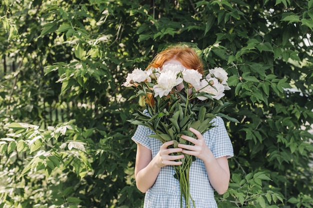 赤い髪の少女は、牡丹の花束で顔を覆った。