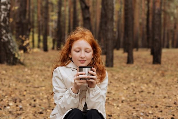 Рыжая девушка пьет чай в лесу, сидя на бревне.