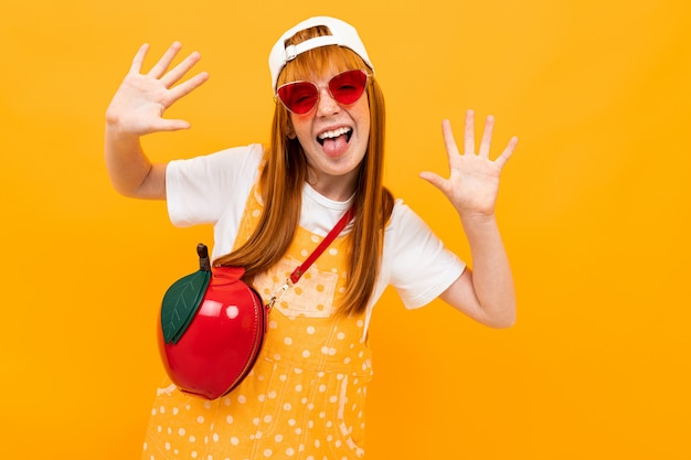 Red-haired girl in glasses with a red handbag in the shape of an apple is grimacing at the camera on a yellow banner background