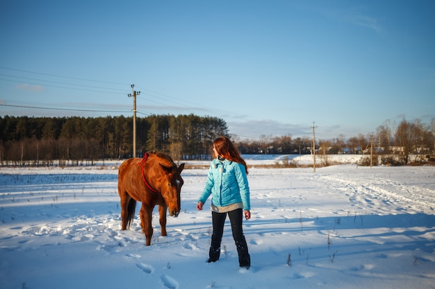 Red-haired girl goes with a horse in a snowy field
