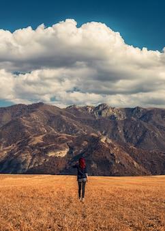Ragazza dai capelli rossi nei campi dorati con le montagne rocciose sullo sfondo