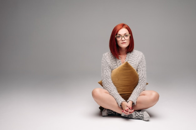 Red haired girl in grey sweater and warm socks sitting on floor