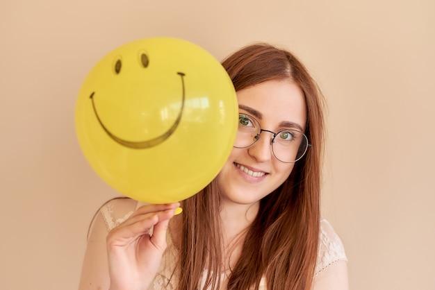 베이지색 배경에 미소와 함께 노란 풍선을 들고 나가서는 소녀