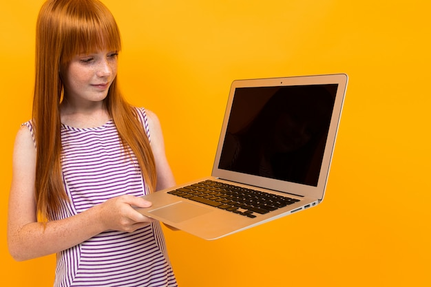 Red-haired girl holding a laptop in his hands on a yellow background