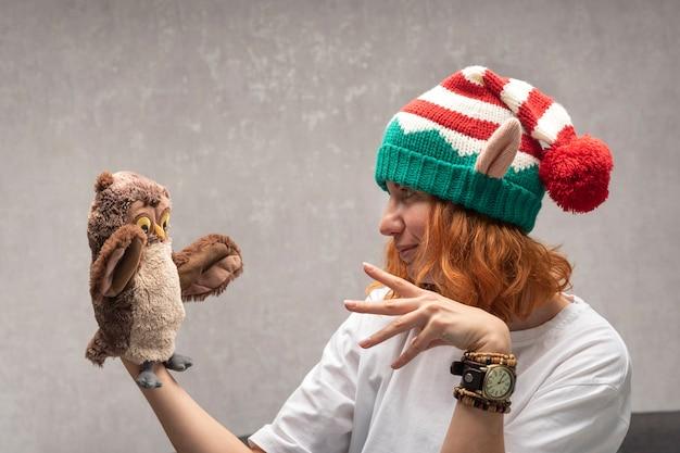 Рыжая девушка в шляпе эльфа разговаривает с игрушкой. смешная девочка и игрушечная сова. кукольный театр.