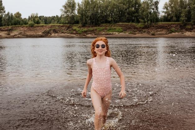 Рыжая девушка в темных очках выбегает из воды на пляже.