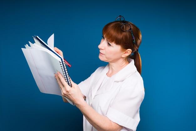 医療服を着た赤い髪の少女は、青い背景で隔離のレコードのノートに書き込みます