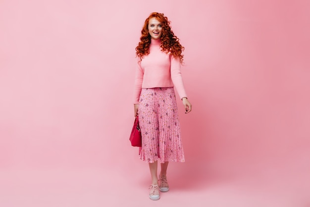 Рыжая девушка в розовой юбке и свитере позирует с яркой сумкой на изолированной стене
