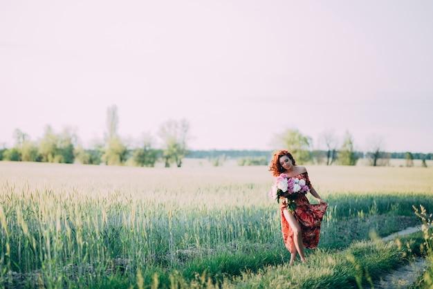 Рыжеволосая девушка в красном платье с букетом пионов, прогуливаясь по пути в летнее поле на закате.