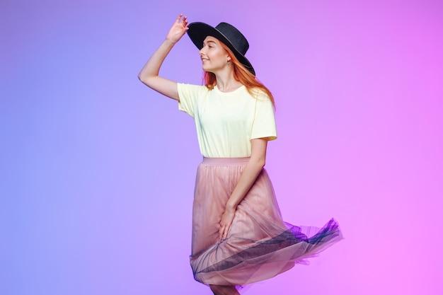 風の中の赤毛の少女は帽子をかぶっています