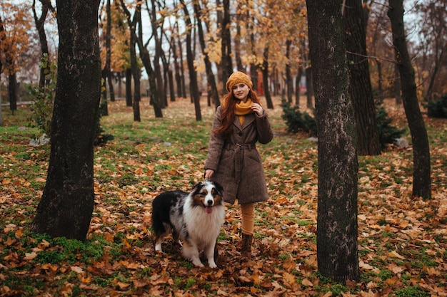 Рыжая девушка в желтом лесу с собакой