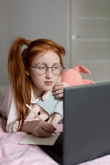 赤い髪の少女は、コロナウイルスのパンデミックのために自宅教育を受けています。