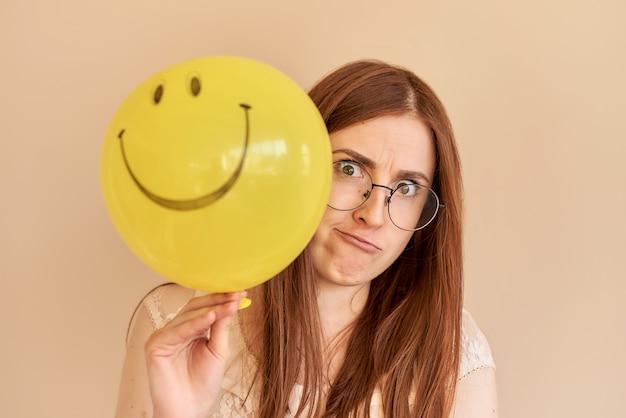 빨간 머리 소녀는 행복하지 않고 베이지색 배경에서 노란색 풍선을 들고 있다