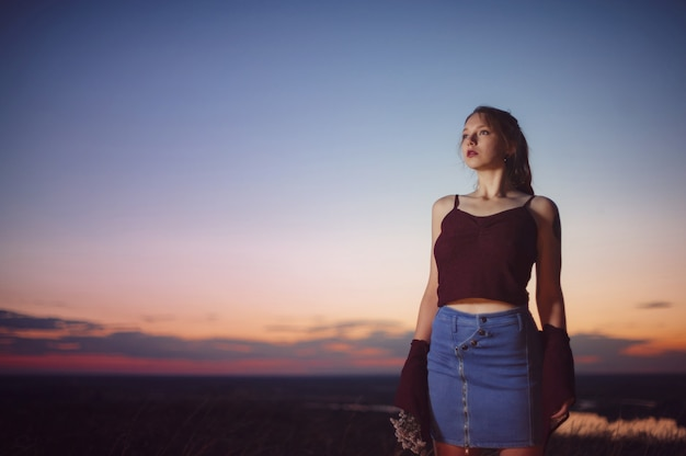 Red haired girl is standing on brink of precipice at sunset.