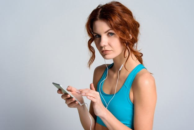 Red haired girl is texting message on the phone.