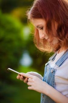 赤毛の少女がモバイルパークでメッセージを入力しています