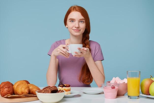 Ragazza dai capelli rossi isolata sulla parete blu, seduto a un tavolo, tiene la tazza bianca con una bevanda deliziosa nelle mani