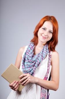 Рыжая девушка держит книгу в руке.