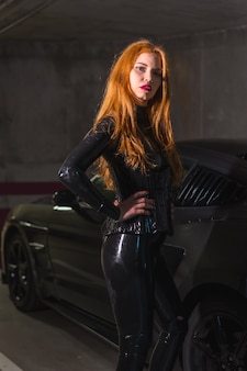 Red-haired girl in latex, a black top and tight pants, leaning on a sports car in a garage