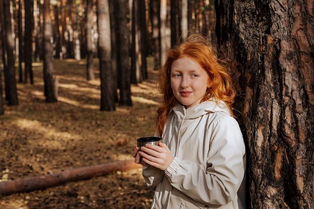 Рыжая девушка, прислонившись к дереву, пьет чай в осеннем лесу.