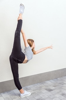 Рыжая девушка поднимает ногу в балетной позе с белыми тапочками, черными брюками и серой футболкой с элегантно вытянутой рукой