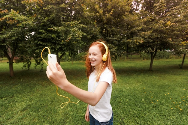Red-haired girl listens to lessons with headphones. lying on the grass.