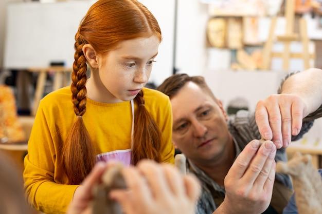 Рыжая девушка смотрит на учителя лепит из глины