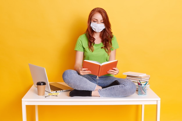 Red haired girl in medical mask sits on table with computer and books, reading, looks concentrated