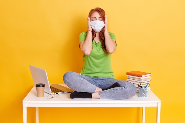 Red haired girl in medical mask sits with crossed legs on white table, covering her ears with palms and keeps eyes closed, wearing jeans and t shirt, surrounded with lap top, coffee, pens