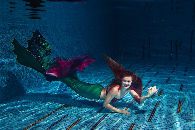 Red-haired girl in a mermaid costume underwater in the pool