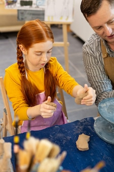 Red-haired girl modeling clay figures with teacher