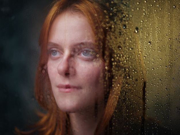 Red-haired girl near a rainy window