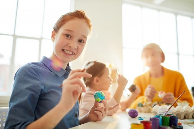 イースターの卵を塗る赤い髪の少女