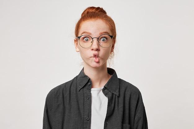 赤毛の少女は、広い目で眼鏡を通して見ている彼女の唇で魚を描いています