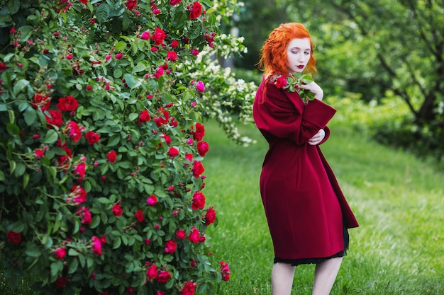 The red-haired girl in red coat posing on a background of a bush with red roses