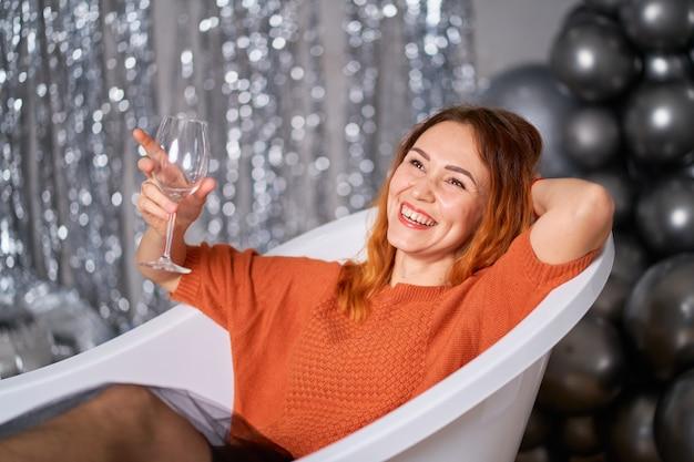 赤毛の女の子はお風呂に身を包んで座って喜ぶ