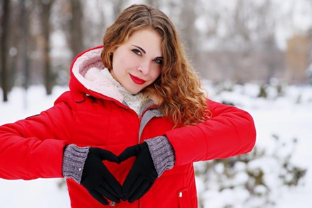 발렌타인 데이에 그녀의 손으로 마음을 보여주는 나가서는 소녀 프리미엄 사진