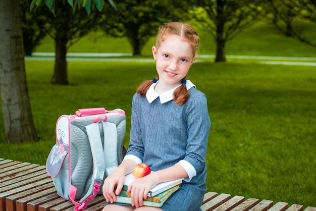 Red-haired girl sits on a bench, is smiling. student in school uniform. back to school, young girl ready for class. school bag and apple