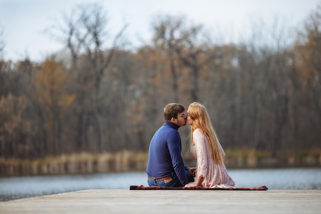 Red-haired girl sits with a guy in an embrace on a pier near the lake with a beautiful view