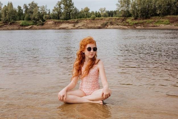 Рыжая девушка сидит в позе лотоса на мелководье.