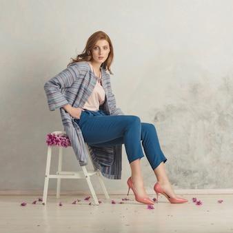 彼女の周りの花と脚立に座っている赤い髪の少女