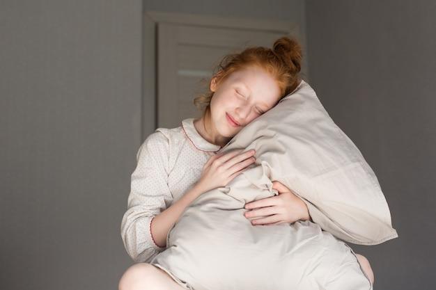赤い髪の少女が眠そうに枕を抱きしめます。