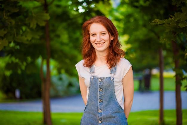 立って笑っている赤毛の少女