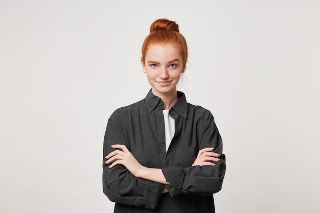 La ragazza dai capelli rossi sta con le braccia incrociate con un civettuolo