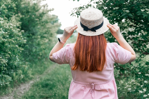 Red haired girl in straw hat in the garden, back view