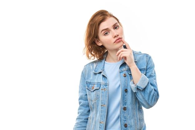 Рыжая студентка задумчиво смотрит, держа руку возле лица. молодая женщина в синей джинсовой куртке на белом фоне думает, что выбрать