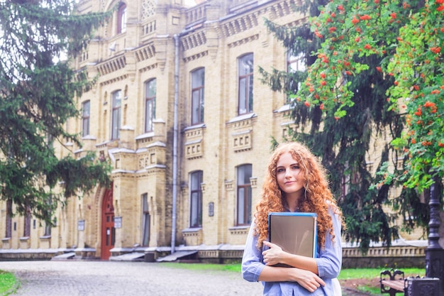 Red-haired girl student with folders and teaching materials in hands