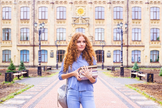 Red-haired girl student with a pile of books coming from the university library