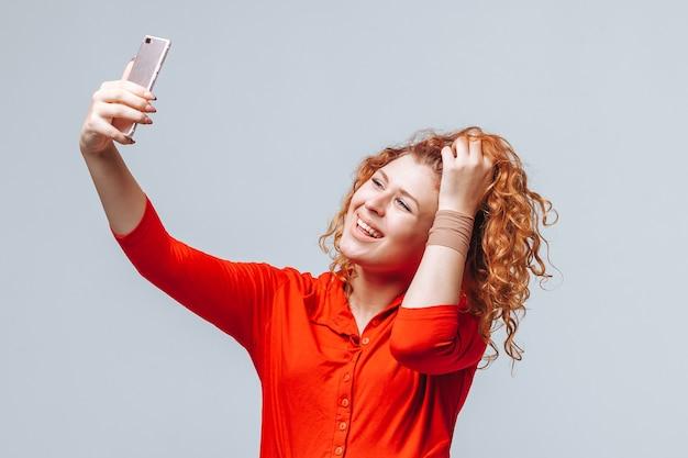 赤髪の少女は明るい灰色の背景に電話で自分撮りをします